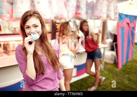 Portrait of teenage girl eating Cotton Candy avec des amis en arrière-plan Banque D'Images