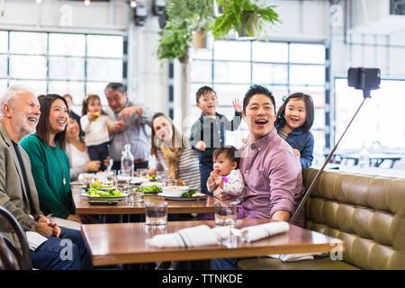 Famille heureuse de prendre tout en dînant en selfies restaurant Banque D'Images