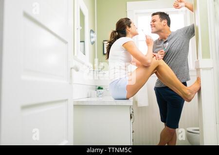 Couple se brosser les dents dans la salle de bains Banque D'Images