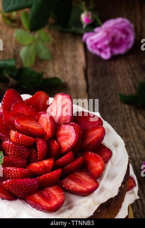 Buttercream fait maison avec des fraises, gâteau table de fête avec des roses et des baies, fond en bois rustique Banque D'Images