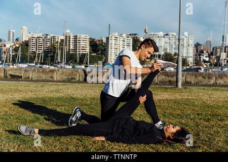 Petit ami aider son amie en étirant la jambe contre cityscape Banque D'Images