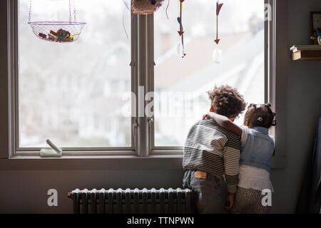 Vue arrière de la fratrie à la fenêtre grâce à à la maison Banque D'Images