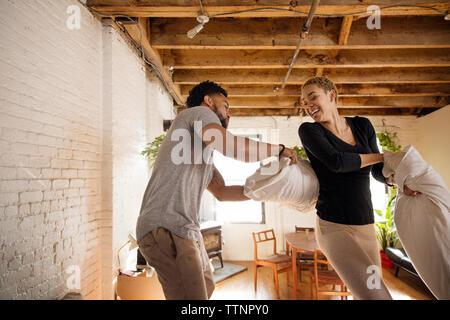 Happy young couple having pillow fight dans la chambre Banque D'Images