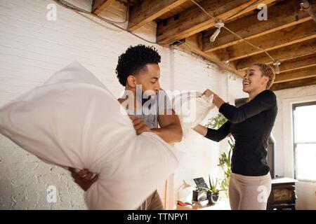 Cheerful couple having pillow fight dans la chambre Banque D'Images