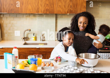 Mère portant son daughter making cupcakes dans la cuisine Banque D'Images