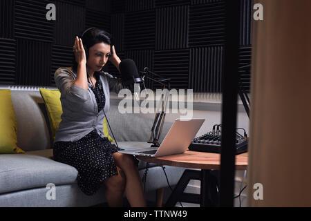 Businesswoman adjusting écouteurs en vidéo conférence dans Office Banque D'Images