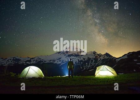Vue arrière de l'homme debout sur le terrain par tentes contre ciel étoilé Banque D'Images