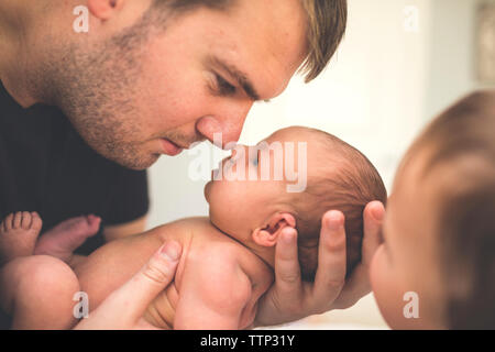 Father carrying newborn fille assis par fils à la maison Banque D'Images