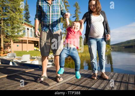 Fils jouant avec les parents sur l'embarcadère en bois sur le lac Banque D'Images