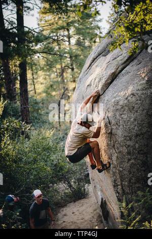 Portrait d'amis à la recherche au randonneur climbing rock formation in forest Banque D'Images