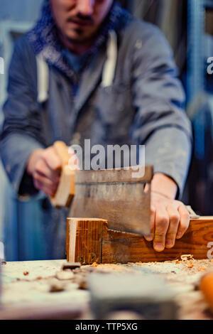 Portrait male carpenter scier du bois en atelier Banque D'Images