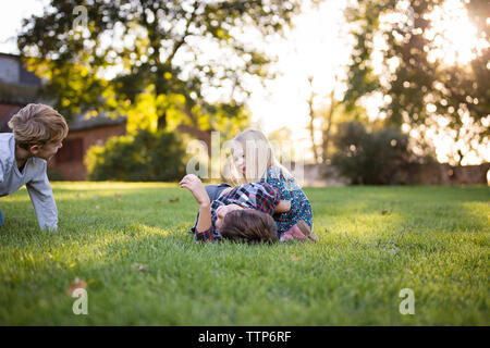 Frères et sœurs jouant et riant dans les champs en plein air Banque D'Images