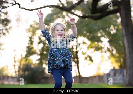 Fille blonde sauter avec les bras dans l'air extérieur et grand sourire