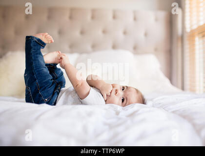 Cute baby boy laying on bed accaparement des orteils et la main dans la bouche Banque D'Images