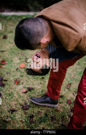 High angle view of playful père exerçant son fils heureux en se tenant sur le terrain d'herbe dans le Parc Balboa