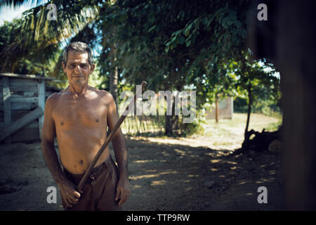 Portrait of shirtless man holding stick en se tenant sur le terrain Banque D'Images
