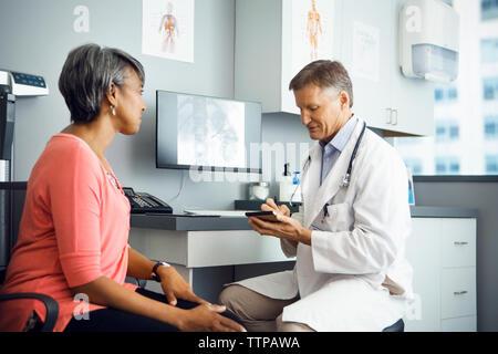 Médecin homme écrit prescription pour female patient in clinic Banque D'Images