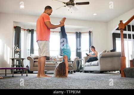 Father helping daughter doing handstand dans la salle de séjour à la maison Banque D'Images