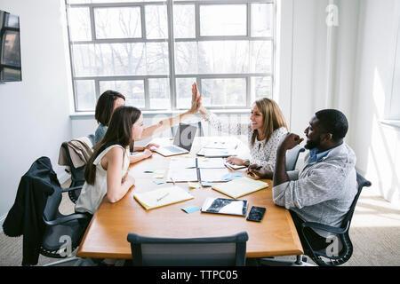 Les femmes d'affaires heureux fiving haut alors qu'il était assis avec des collègues dans la salle du conseil Banque D'Images