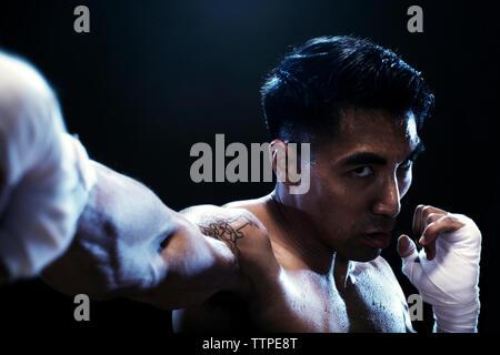 Portrait de déterminé kickboxer pratiquant sur fond noir Banque D'Images