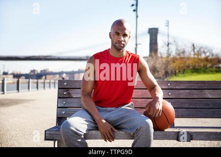 Portrait de joueur de basket-ball assis sur un banc à la promenade Banque D'Images