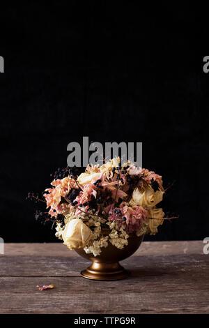 Close-up de vase de fleurs sur table en bois sur fond noir