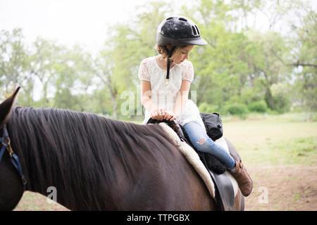 Jeune fille à la recherche vers le bas tandis que l'équitation à la ferme Banque D'Images