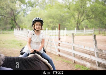 Fille à la voiture tandis que l'équitation au Ranch Banque D'Images