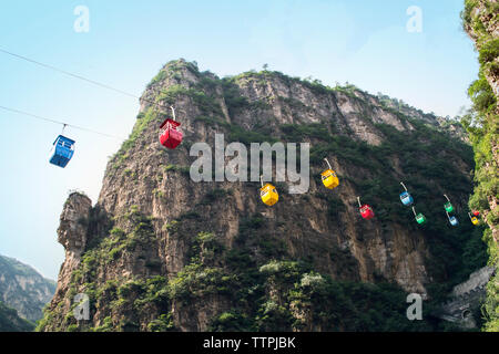 Low angle view of overhead cable cars contre montagne