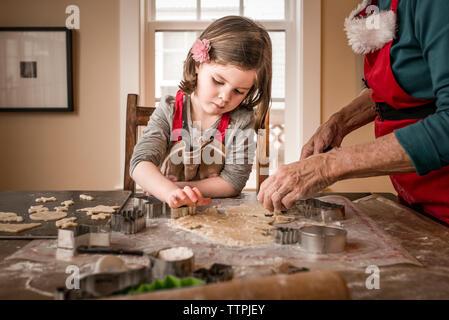 Petite-fille d'aider grand-mère à faire les biscuits de Noël sur la table à la maison Banque D'Images