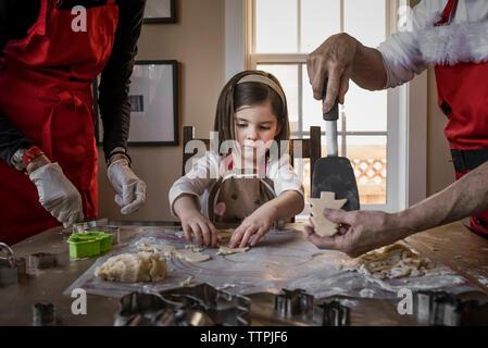 Petite-fille d'aider les grands-parents à faire les biscuits de Noël sur la table à la maison Banque D'Images