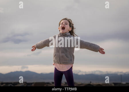 Happy girl with arms outstretched hurlant debout contre ciel nuageux