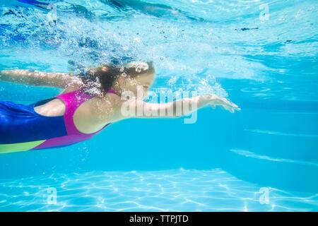 Vue latérale du girl swimming underwater Banque D'Images