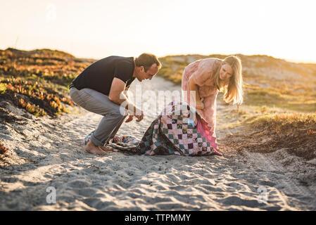 Heureux parents regardant cute fils visés dans le contrat cadre tout en restant assis sur la plage contre un ciel clair pendant le coucher du soleil Banque D'Images