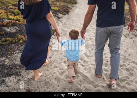 La section basse des parents tenant les mains de son fils tout en marchant sur le sable à la plage pendant le coucher du soleil Banque D'Images