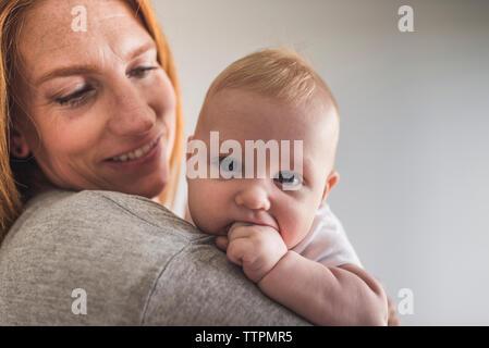 Close-up of mother carrying mignon fils avec les doigts dans la bouche alors qu'il se tenait contre le mur gris à la maison Banque D'Images