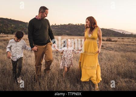 Jeune famille tenant la main tout en marchant en Californie field at sunset