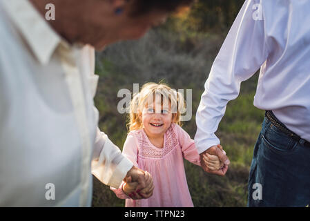 Little girl holding hands with parents, looking up and smiling