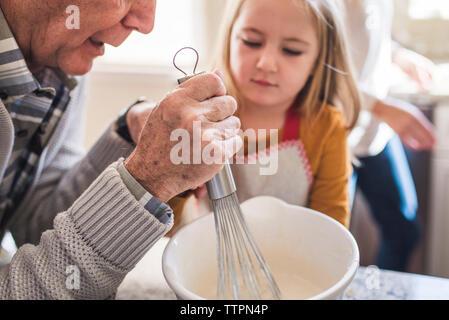 Fille et granddfather ce qui fait du petit déjeuner de crêpes dans la cuisine