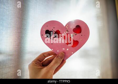Portrait of hand holding heart shape artwork fenêtre contre Banque D'Images