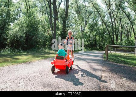 Fille poussant frère assis dans le parc à voiture jouet Banque D'Images