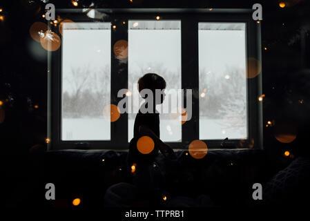 Vue latérale du garçon à la silhouette illuminée en prix à la maison Banque D'Images