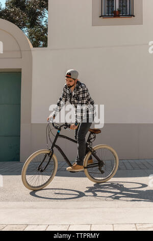 Homme confiant équitation location sur la rue contre le bâtiment au cours de journée ensoleillée Banque D'Images