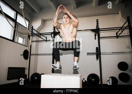 Toute la longueur du torse nu jeune homme sautant sur fort tout en faisant de l'exercice dans la salle de sport Banque D'Images