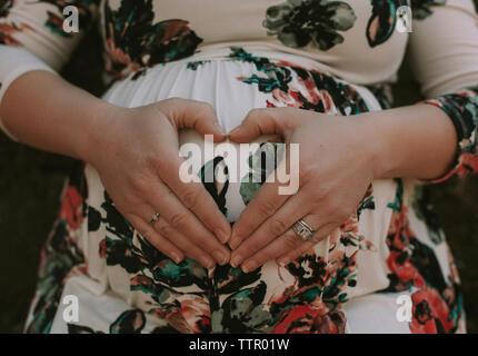 Portrait de femme enceinte en forme de cœur sur son ventre avec les mains Banque D'Images