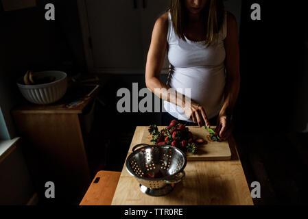Future maman, couper les fraises dans la cuisine dans des conditions de faible luminosité Banque D'Images