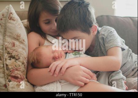 Frères et sœurs à la recherche de baby boy while sitting on sofa Banque D'Images