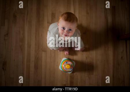 Overhead portrait of cute baby boy with toy assis sur le plancher à la maison Banque D'Images