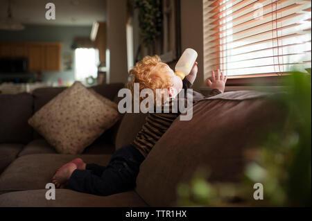 Vue latérale du baby boy boire du lait tout en vous relaxant sur canapé par fenêtre à la maison Banque D'Images