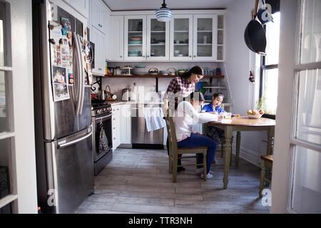 Aider les filles pour l'étude de femme à table dans la cuisine